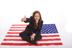 Girl sited on the american flag Stock Photography