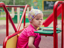 Girl siting Carouse. Little girl on a Carnival Carousel at an amusement park or theme park. Warm afternoon sun in the background Royalty Free Stock Photography