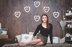 A girl siting with hearts on the backgound. A girl siting on the floor with hearts on the backgound Stock Photos