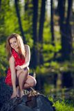 Girl siting on a log Stock Images