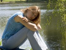 Girl siting near pond Stock Photography