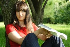 Girl siting near tree and reading book Stock Photography