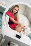 Girl siting in a white chair Stock Photography