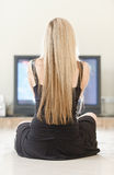Girl sits against big TV Royalty Free Stock Image