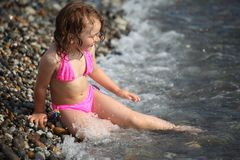 Girl sits ashore in waves Stock Images
