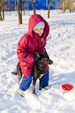 Girl sits astride the dog. Girl sits astride a black dog on a snowy winter Stock Photo