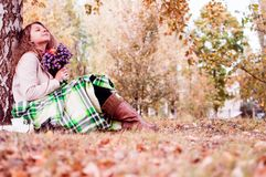 The girl sits on the autumn grass, reading a book stock photo