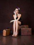 Girl sits on a bag Stock Image