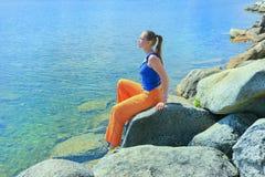 Girl sits on bank of lake Stock Images