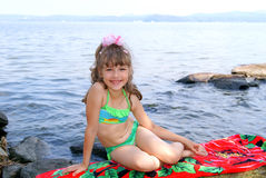 The girl sits on a beach. The nice smiling girl in a green bathing suit sunbathes in the summer on the bank of lake Stock Photo