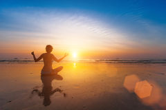 A girl sits on the beach in a yoga pose at sunset. Nature. Royalty Free Stock Photography