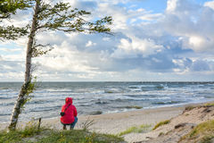 Girl sits on the beachfront and looks into the distance Royalty Free Stock Image