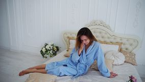 Women in Bad Mood, Upset and Crying, Sitting on Bed in Spacious Bedrooms. Girl Sits on Beautiful Double Bed and Sad, Crying Because of Failed Plans or Bad Day royalty free stock image