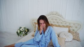 Women in Bad Mood, Upset and Crying, Sitting on Bed in Spacious Bedrooms. Girl Sits on Beautiful Double Bed and Sad, Crying Because of Failed Plans or Bad Day stock photography