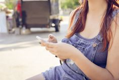 The girl sits on a bench in a blue overalls and holds a mobile p Stock Photos