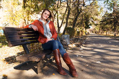 The girl sits on a bench in the park in the fall Stock Image