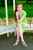 A girl sits on a bench in the park Stock Photo
