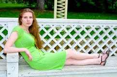 A girl sits on a bench in the park Stock Photography