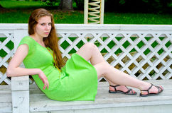 A girl sits on a bench in the park Stock Images