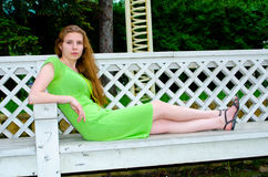 A girl sits on a bench in the park Royalty Free Stock Image