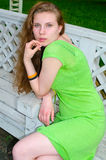 A girl sits on a bench in the park Stock Image