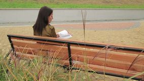 Girl Reads On A Bench. Girl sits on a bench and reads a book back view with some high grass in foreground 1080p, 25fps stock footage