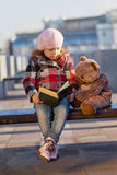 Girl sits on a bench and reads the book. To a toy bear Stock Photos