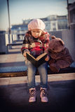 Girl sits on a bench and reads the book. To a toy bear Royalty Free Stock Image