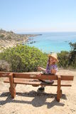 Girl sits on a bench on the coast of the Mediterranean Sea Royalty Free Stock Image