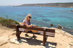 Girl sits on a bench on the coast of the Mediterranean Sea Royalty Free Stock Photo
