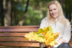 Girl sits on a bench and smiles autumn day Royalty Free Stock Photos