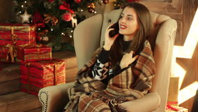 A girl sits in a big chair near a Christmas tree and keeps the phone stock video footage