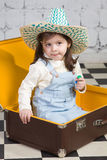 Girl sits in the big road suitcase Stock Photos