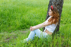 Girl sits at a birch in  forest Royalty Free Stock Photo