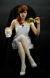 Girl sits in black chair with a rose and skull Royalty Free Stock Photos