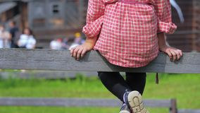 The girl sits on the board of paddock for horses. The girl sits on the board of paddock for horses on the farm or in the village stock footage