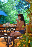 A girl sits in a cafe and drinking tea Royalty Free Stock Images