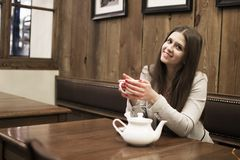 The girl sits in a cafe and holds a cup in her hands stock photos