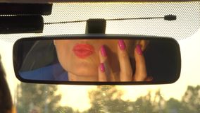 Girl sits in car and looks in mirror. She touches chin and makes sure lipstick on lips is fine. Girl makes the final stock footage