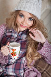 A girl sits in a chair with cup of coffee or tea Royalty Free Stock Photos
