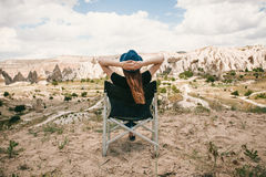 The girl sits on a chair, relaxes and admires an amazing view of the hills of Cappadocia in Turkey. Relaxation, rest Royalty Free Stock Images