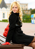 Girl sits on city bench. Beautiful woman in black coat and red bag against city Royalty Free Stock Images