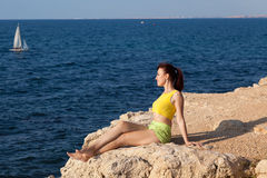 Girl sits on a cliff and looking at the sea Stock Photography