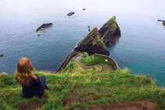 Girl sits on a cliff over the ocean in Ireland stock photo