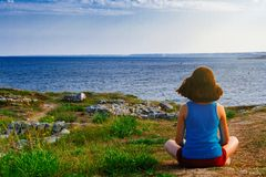 Girl sits on the coast and looks at the sea. royalty free stock photography