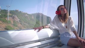 The girl is looking out the funicular window. A girl sits in the cockpit of a funicular with a red flower on her head stock video