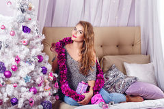 Girl sits on a couch near Christmas tree. Royalty Free Stock Photos