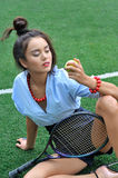 Girl sits on the court with racket and holding a tennis ball. Stock Images