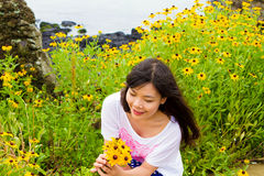 Girl sits in daisy sunflower field near the beach Royalty Free Stock Image