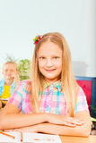 Girl sits at desk with hands on exercise book Royalty Free Stock Photography